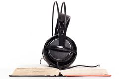 Headphones and book on a white background Royalty Free Stock Image