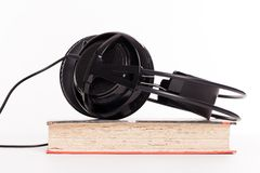 Headphones and book on a white background Royalty Free Stock Photos