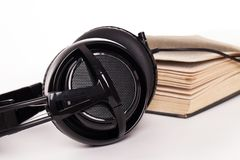 Headphones and book on a white background Stock Photos