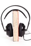 Headphones and book on a white background Royalty Free Stock Photo