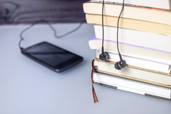 Headphones on books and flying notes. The concept of audiobooks. Black headphones on a stack of books and flying notes. The concept of audiobooks Royalty Free Stock Image