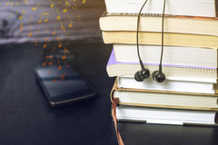 Headphones on books and flying notes. The concept of audiobooks. Black headphones on a stack of books and flying notes. The concept of audiobooks Stock Photos