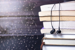 Headphones on books and flying notes. The concept of audiobooks royalty free stock image