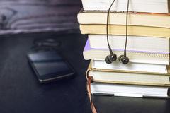 Headphones on books and flying notes. The concept of audiobooks. Black headphones on a stack of books and flying notes. The concept of audiobooks Royalty Free Stock Photo