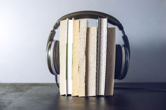 Headphones on books and flying notes. The concept of audiobooks. Black headphones on a stack of books near flying notes. The concept of audiobooks Stock Images