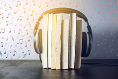 Headphones on books and flying notes. The concept of audiobooks. Black headphones on a stack of books near flying notes. The concept of audiobooks Stock Photo
