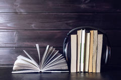Headphones on books and flying notes. The concept of audiobooks. Black headphones on a stack of books near open book and flying notes. The concept of audiobooks Stock Image