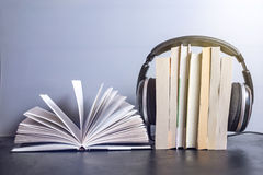 Headphones on books and flying notes. The concept of audiobooks. Black headphones on a stack of books near open book and flying notes. The concept of audiobooks Royalty Free Stock Photos
