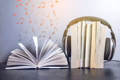 Headphones on books and flying notes. The concept of audiobooks. Black headphones on a stack of books near open book and flying notes. The concept of audiobooks Stock Images