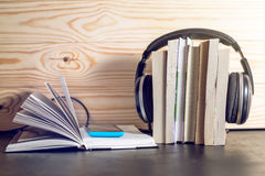 Headphones on books and flying notes. The concept of audiobooks. Black headphones on a stack of books near open book with a phone where audio is playing and Royalty Free Stock Photo