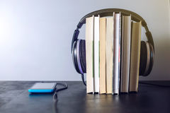 Headphones on books and flying notes. The concept of audiobooks. Black headphones on a stack of books near a phone where audio is playing and flying notes. The Stock Image