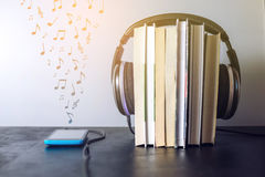Headphones on books and flying notes. The concept of audiobooks. Black headphones on a stack of books near a phone where audio is playing and flying notes. The Royalty Free Stock Photography