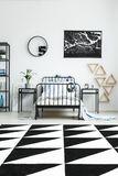 Headphones on boy`s bed. In white bedroom with triangles, clock and dark poster on wall Stock Image
