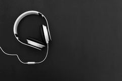 Headphones and cable on a dark background. Top view. Stock Image