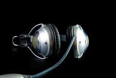 Headphones with cable and reflaction. Isolated on black stock images