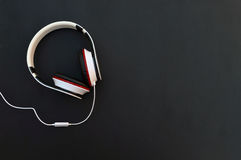 Headphones and cable on a wooden background. Top view. Royalty Free Stock Images