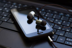Headphones and  cell phone at the keyboard. Photo serie with Headphones and mobile phone at the keyboard background Stock Images