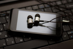 Headphones and  cell phone at the keyboard. Photo serie with Headphones and mobile phone at the keyboard background Royalty Free Stock Photography
