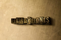 HEADPHONES - close-up of grungy vintage typeset word on metal backdrop Royalty Free Stock Images