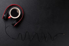 Headphones and coffee cup on desk Stock Photography
