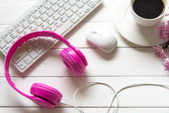 Headphones and coffee cup on wooden desk table with pink flower. Music and lifestyle concept.