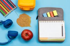 Headphones, color pencils, apple, dry leaf, lunch box, open exer. Cise book on bag-pencil case with color felt pens and marker on blue background. Top view. Back stock image