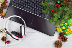 Headphones, computer and Christmas tinsel. Holiday melodies. Royalty Free Stock Images