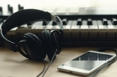 Headphones are connected to the phone. The headphones are connected to the phone lying next to the synthesizer on a beige background. Against the background of Stock Photo