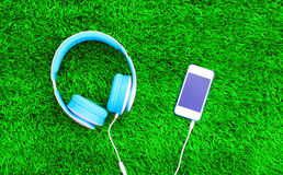 Headphones connected to white smartphone on a green grass. Textured background Stock Photography
