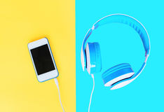 Headphones connected to white smartphone over colorful yellow Stock Photos