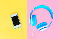 Headphones connected to white smartphone over colorful yellow pink Stock Images