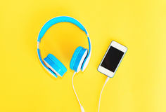 Headphones connected to white smartphone over yellow Royalty Free Stock Photography