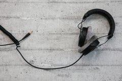 Headphones with cord. Black headphones with cord on concrete background stock photos