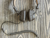 Headphones with cord lying on wooden background. Stock Photo