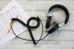 Headphones with cord and music sheet. Black headphones with cord and music sheet on concrete background royalty free stock image
