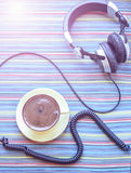 Headphones and cup with coffee on the colorful tablecloth Royalty Free Stock Photos