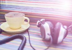 Headphones and cup with coffee on the colorful tablecloth Stock Photo