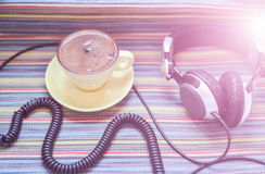 Headphones and cup with coffee on the colorful tablecloth Stock Image