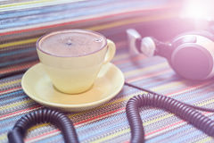 Headphones and cup with coffee on the colorful tablecloth Stock Images