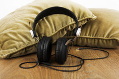 Headphones on cushions on a wooden surface Royalty Free Stock Photography
