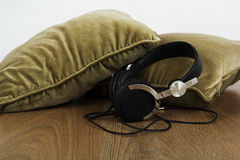 Headphones on cushions on a wooden surface Stock Images