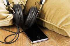 Headphones on cushions on a wooden surface Royalty Free Stock Photos