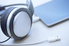Headphones digital tablet and USB cable Royalty Free Stock Photography