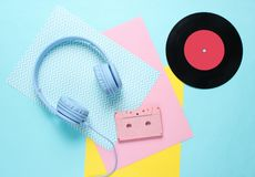 Headphones and earphones with audio cassettes. On colored paper backgrounds. Retro style, minimalism. Flat lay. Top view royalty free stock image