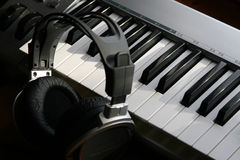 Headphones & Electric Piano. Photograph of headphones resting next to a electric keyboard stock image