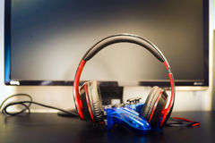 Headphones and gamepad. Gamepad  and  headphones lie against the backdrop of the monitor Royalty Free Stock Photo