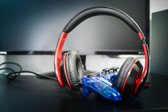 Headphones and gamepad. Gamepad  and  headphones lie against the backdrop of the monitor Stock Image
