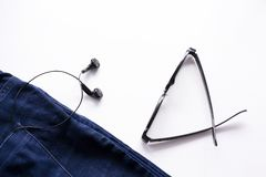 Headphones and glasses in the jeans pocket on a white background stock images