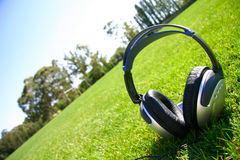 Headphones with grass and sky. Silver headphones with grass and sky in backgrond Royalty Free Stock Photography
