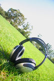 Headphones with grass and sky. Silver headphones with grass and sky in backgrond Stock Images